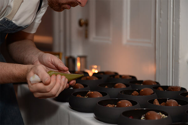 a close up shot of a chef squeezing toppings onto black bowls of chocolate iced cream with a pastry bag